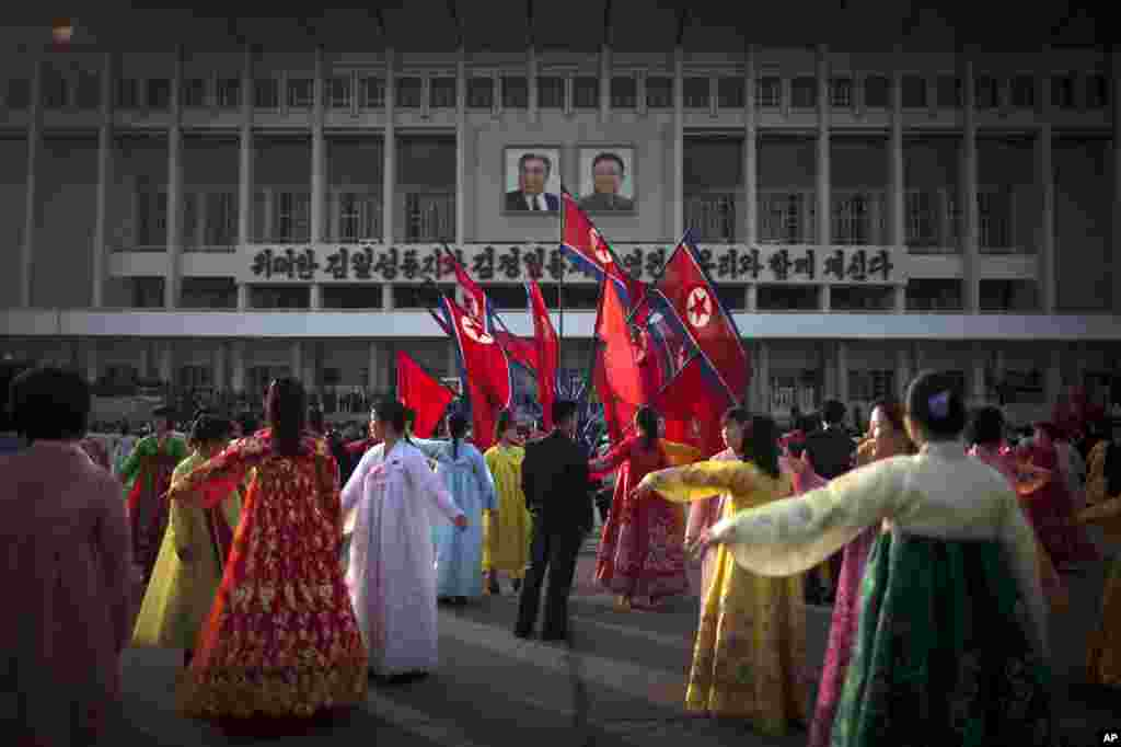 A man, center, supervises a dancing group during a mass folk dance in front of the Pyongyang Indoor Stadium, April 15, 2013.