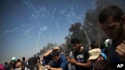 Des dizaines de bombes lacrymogènes tirées par les troupes israéliennes tombent sur des manifestants palestiniens à la frontière de la bande de Gaza avec Israël, vendredi 8 juin 2018. (Photo AP / Khalil Hamra)