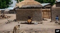 Une femme non identifiée est aperçue devant sa maison à Chibok, village d'où les combattants ont enlevé 276 lycéennes le 14 avril 2014, au Nigeria. Photo : 19 mai 2014.