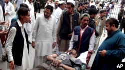 People stand near a man injured from an explosion, at a local hospital in Pakistani tribal area of Parachinar, May 6, 2013.