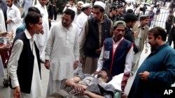 Warga Parachinar, Pakistan, berdiri dekat korban luka akibat ledakan bom. (Foto: Dok)
