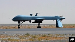 FILE - A U.S. Predator unmanned drone armed with a missile stands on the tarmac of Kandahar military airport in Afghanistan, June 13, 2010.