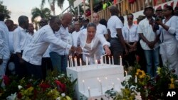 Haiti's new Prime Minister Evans Paul, left center, Haiti's President Michel Martelly, center, and first lady Sophia Martelly, lead a vigil at the site of a high-voltage wires' accident that left at least 16 people dead, in Port-au-Prince, Haiti, Feb. 17,