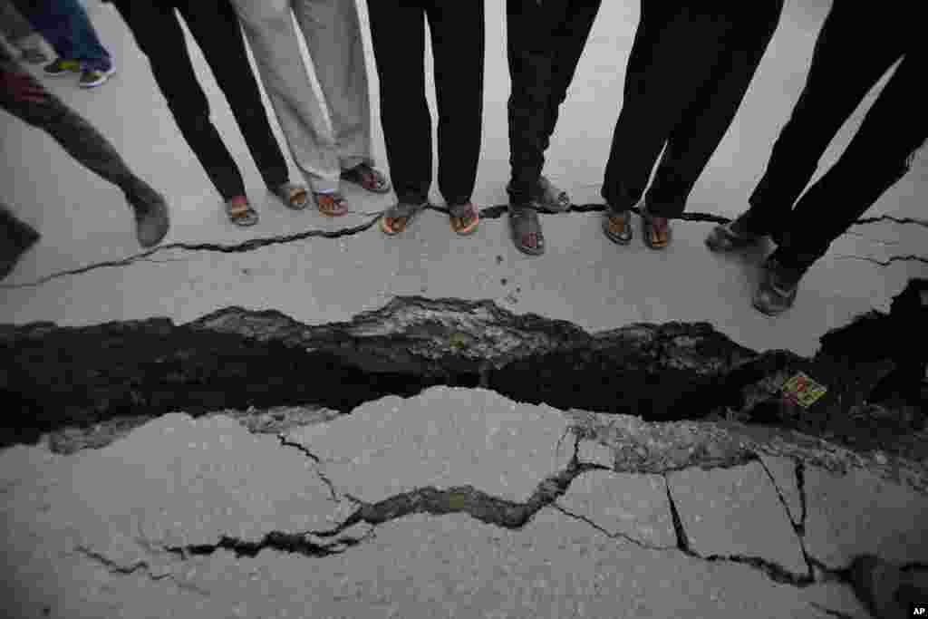 Nepalese people look at a cracked road after an earthquake in Kathmandu, Nepal, April 26, 2015.