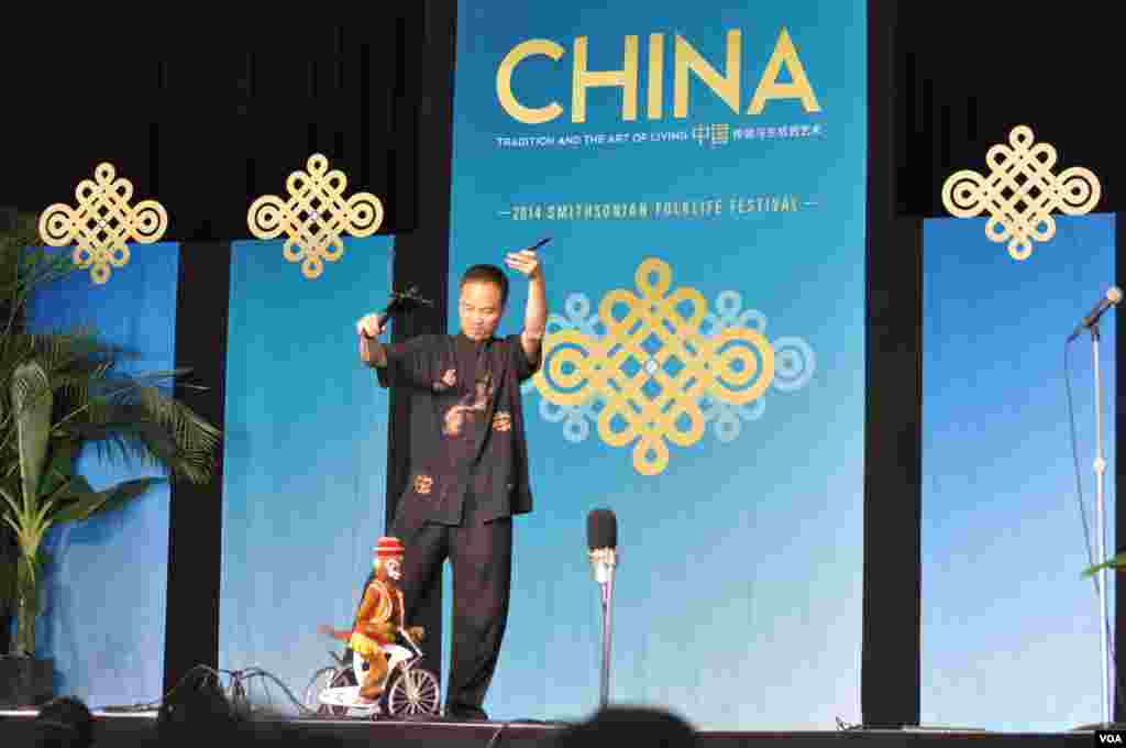 A Chinese puppeteer entertains the crowd with the antics of his monkey on a bicycle at the Smithsonian Folklife Festival in Washington, June 25, 2014. (Regina Catipon/VOA)