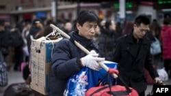 Một hành khách gánh hành lý chờ lên xe lửa tại một nhà ga ở Bắc Kinh