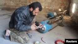 FILE - A Free Syrian Army fighter prepares a locally made shell before firing it toward forces loyal to Syria President Bashar al-Assad in Bani Zeid neighborhood, Aleppo, Nov. 10, 2014.