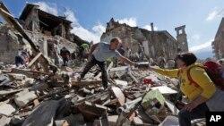 Para petugas mencari penyintas di bawah puing-puing akibat gempa di kota Amatrice, Italia tengah (24/8). (AP/Alessandra Tarantino)
