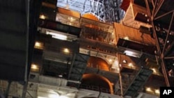 This image provided by NASA shows space shuttle Discovery with it's external fuel tank being worked on and examined in the Vehicle Assembly Building at NASA's Kennedy Space Center in Florida. NASA decided to delay the launch and allow the teams additional