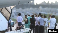 Chinese activists detained after landing on a disputed island are escorted by airport officials as they board a flight to Hong Kong, in this photo taken by Kyodo August 17, 2012.