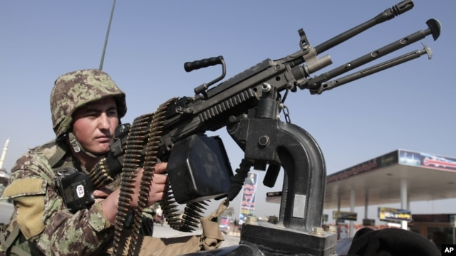 Afghan National army soldier takes on a weapon during a patrol near prayers gather for Eid al-Adha near a mosque in the outskirt of Jalalabad east of Kabul, Afghanistan, October 26, 2012.