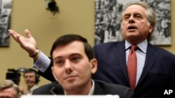 Benjamin Brafman, right, attorney for pharmaceutical chief Martin Shkreli, foreground, speaks on Capitol Hill in Washington, Feb. 4, 2016, during a House Committee on Oversight and Reform Committee hearing on rising drug prices.
