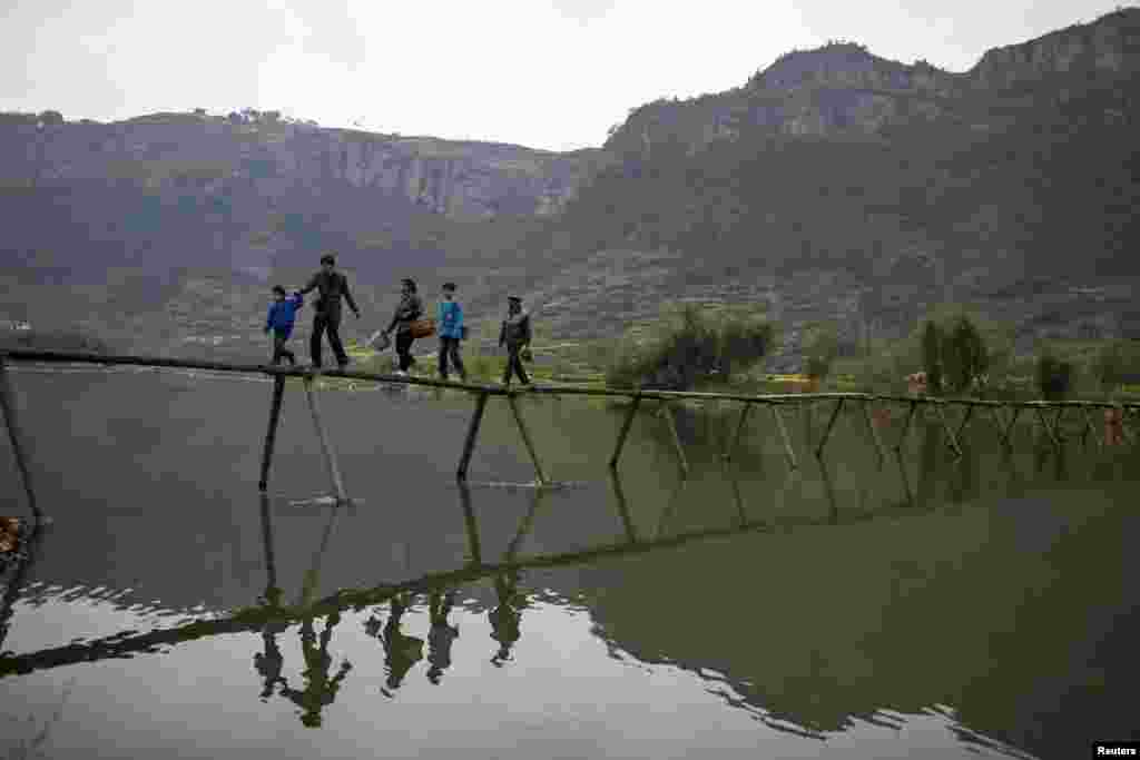 Locals walk on a bridge as they go to a tea plantation in Xinchang, Zhejiang province, China.