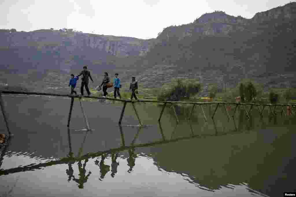 Người dân địa phương băng qua cầu tới đồn điền trồng trà ở huyện Tân Xương, tỉnh Chiết Giang, Trung Quốc.