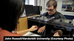 "The ""rubber hand illusion"" has been used in psychological experiments for nearly two decades. Here, at Vanderbilt University, a researcher uses a pair of brushes to test a participant's perception. (Vanderbilt University / John Russell)"