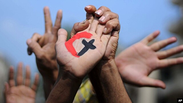 A cross and a crescent are painted on the palm of an Egyptian demonstrator holding the hand of a fellow protester during a rally in support of national unity in Cairo's Tahrir Square on October 14, 2011.