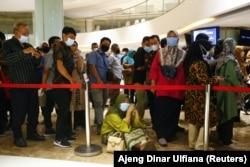 Seorang perempuan duduk di lantai saat dia mengantre untuk menerima dosis vaksin Sinovac China di sebuah pusat perbelanjaan di Jakarta, 1 April 2021. (Foto: REUTERS /Ajeng Dinar Ulfiana)