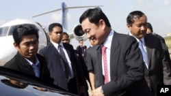 Former Thai Prime Minister Thaksin Shinawatra, center, gets on a car upon his arrival at a military air base in Phnom Penh, (file photo).