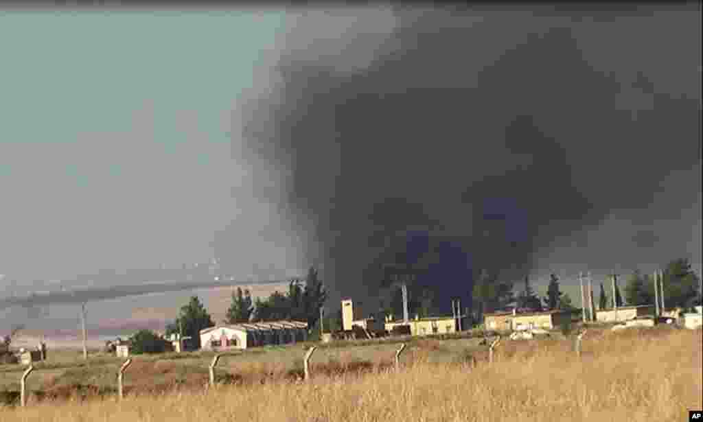 This citizen journalism image provided by ENN shows black smoke rising from what rebels say is a helicopter that was shot down at Abu Dhour military airbase, Idlib, Syria, May 17, 2013.