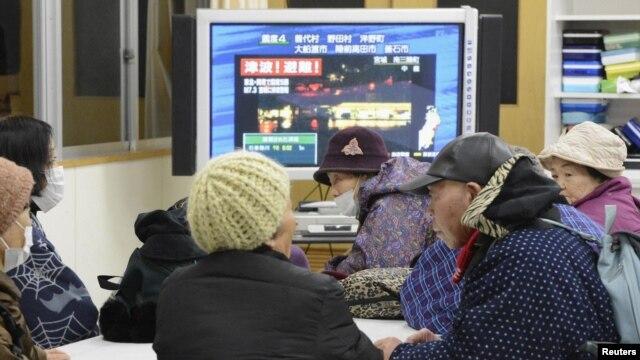 Lokalni stanovnici prate televizijske izveštaje u jednoj školi pretvorenoj u prihvatilište za evakuisane