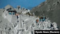Yanardağın kül kaplı sırtlarında arama yapan Japon polisi ve askerleri