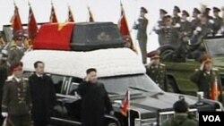 Kim Jong Un berjalan di sebelah peti jenasah mendiang ayahnya dalam prosesi pemakaman Kim Jong Ill di Pyongyang (28/12). Foto diambil dari Sentral Pemberitaan TV Korea Utara.