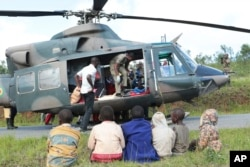 Soldiers and paramedics carry injured people from a helicopter in Chimanimani, about 600 kilometers southeast of Harare, Zimbabwe, March, 19, 2019.
