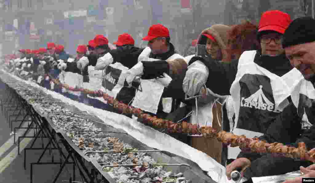 "People cook a giant 150-meter-long ""shashlik"" meal in Kyiv, Ukraine. Participants broke the national record of the longest shashlik cooked during the event. Shashlik is a variety of skewered meat traditionally eaten in the Commonwealth of Independent States (CIS) region."