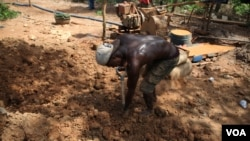A miner uses a shovel to haul dirt at the Atunso Cocoase small-scale mine in Atunso, Ghana, Oct. 16, 2014. (Chris Stein/VOA)