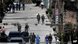 Los trabajadores del Ministerio de Salud están acompañados por soldados y policías mientras investigan en el vecindario acordonado de Lincoln, luego de que varias personas dieron positivo por el nuevo coronavirus, en Tegucigalpa, Honduras.