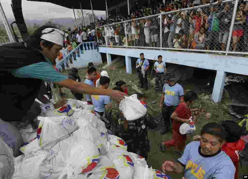 Penyintas topan menerima barang bantuan menyusul kunjungan Presiden Benigno Aquino ke New Bataan, Compostela Valley, Filipina (7/12). (AP/Bullit Marquez)