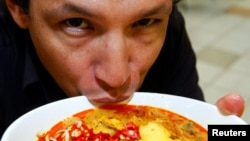 FILE - Chef Bobby Chinn sips from a bowl of Laksa, a dish popular in Singapore hawker centres, while posing for a photo in Singapore.