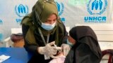FILE - A Rohingya refugee gets vaccinated against COVID-19 in Cox's Bazar, Bangladesh, Aug.10, 2021.