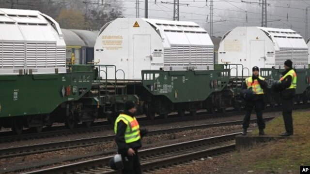 German police guard the train transporting Castor containers, which carry radioactive nuclear waste, during a stop in Neunkirchen near Saarbruecken November 25, 2011.