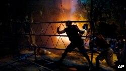 La gente golpea una barrera en el edificio del congreso durante los enfrentamientos entre la policía y los manifestantes que se oponen a una enmienda constitucional aprobada que permitiría la elección de un presidente a un segundo periodo, en Asunción, Paraguay, el 31 de marzo de 2017.