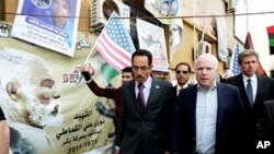 Le sénateur John McCain (à droite) et Abdul Hafiz Ghoqa, porte-parole du Conseil national de transition