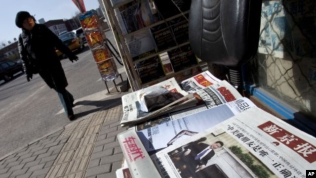 A woman walks past a Beijing newsstand where a newspaper front page shows a photo of Chinese Vice President Xi Jinping and U.S. President Barack Obama, February 16, 2012.