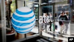 FILE - The AT&T logo is seen on an AT&T Wireless retail storefront in Philadelphia.