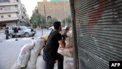 Seorang pemberontak Suriah berjaga di posnya, saat helikopter pemerintah Surah menghujani Aleppo dengan misil (23/7).