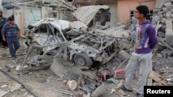 Residents inspect a damaged vehicle at the site of a bomb attack in Kirkuk, 250 km (155 miles) north of Baghdad, March 29, 2013.