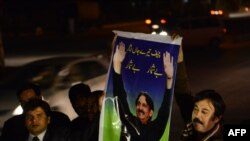 Pakistani lawyers hold up a poster of Supreme Court Chief Justice Iftikhar Muhammad Chaudhry as they mark his retirement outside the Supreme Court building in Islamabad, Dec. 11, 2013.
