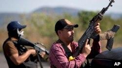 Hombres armados pertenecientes al Consejo de Autodefensas de Michoacán, montan guardia a la entrada del poblado de Antúnez, en México.