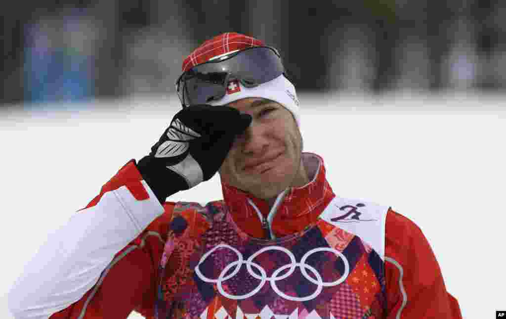 Switzerland's Dario Cologna cries on the podium after winning the gold medal in the men's cross-country 30k skiathlon,Krasnaya Polyana, Russia,Feb. 9, 2014.