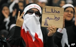 "FILE -A Bahraini female Shi'ite protester holds a sign reading: ""our demands are for country"" during a rally in the village of Diraz, West of Manama, July 1, 2011"