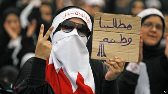 "A Bahraini female Shi'ite protester holds a sign reading: ""our demands are for country"" during a rally in the village of Diraz, West of Manam, July 1, 2011"