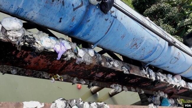 Tumpukan sampah popok di pinggir jembatan Surabaya, yang dibuang sembarangan oleh warga yang tidak bertanggung jawab. (Foto: VOA/Petrus Riski)
