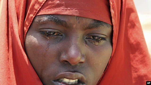 An internally displaced Somali woman mourns near the body of her son, who died of malnourishment, next to their temporary home in Hodan district, south of Somalia's capital Mogadishu, (File).