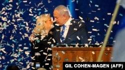 Perdana Menteri Israel Benjamin Netanyahu dan istrinya, Sara, di tengah taburan confetti saat berbicara di depan para pendukungnya, di kantor pusat Partai Likud, di Tel Aviv, 3 Maret 2020.