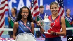 Leylah Fernandez and Emma Raducanu pose with their trophies after the U.S. Open final on Saturday.