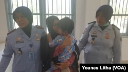 Sambil memeluk anak perempuannya yang berusia satu setengah tahun Asmawati menyerahkan diri ke Lapas Perempuan Kelas III Palu, 30 September 2019. (Foto: VOA/Yoanes Litha)